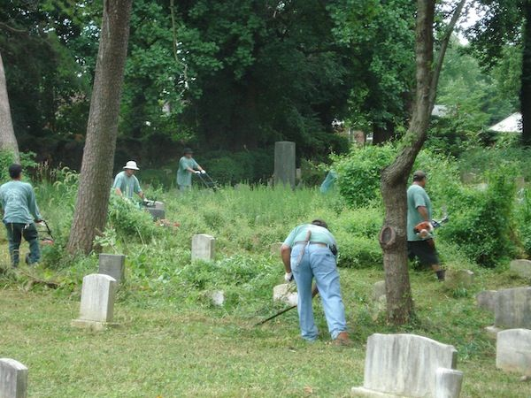 johnson's landscaping crew fixing gravestones on a cemetry