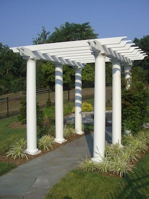 White pergola over a flagstone pathway