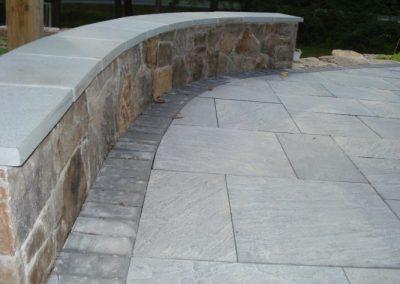 Stone retaining wall alongside stone patio