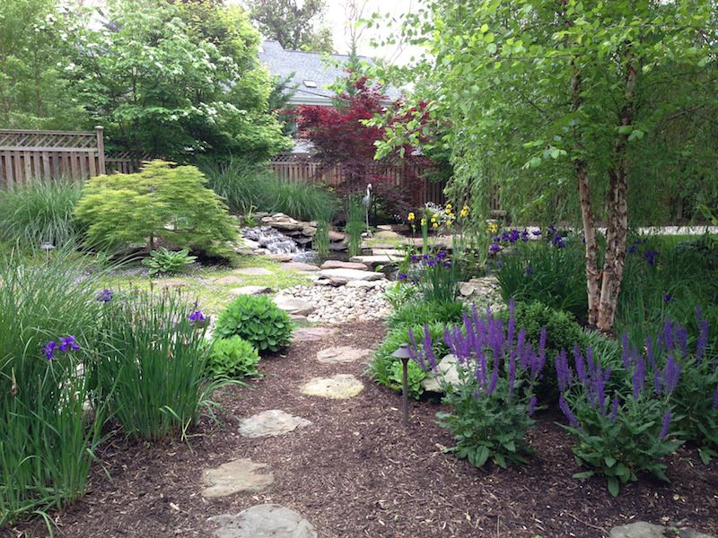 Backyard with waterfall, pond, graveled area, stone walkway, mulch, and plants