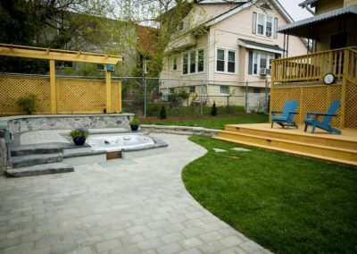 Backyard with stone patio and hot tub, lawn, and raised wooden patio and stairs