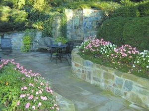 Landscaped backyard patio with stone pavers, decorative retaining walls, and flowers