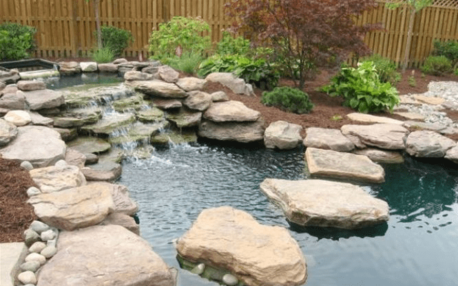 Stones surrounding pond with waterfall