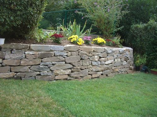 Decorative stone wall in backyard with flowers and greenery