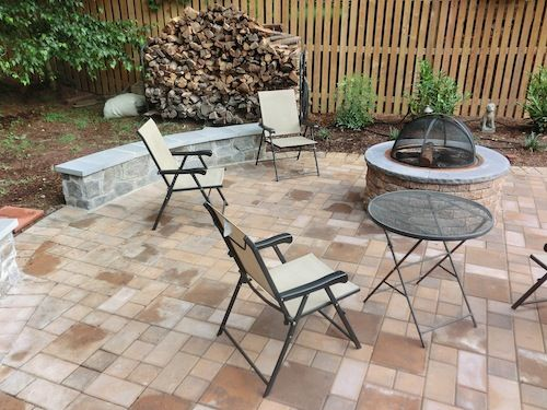 Paved stone patio with stone firepit and deck chairs
