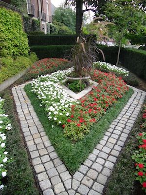 Decorative landscaping in a lawn with stone pavers and flowers
