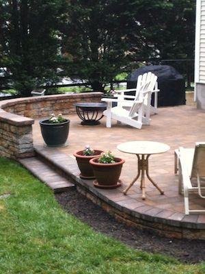 Raised stone outdoor patio with seating area in backyard