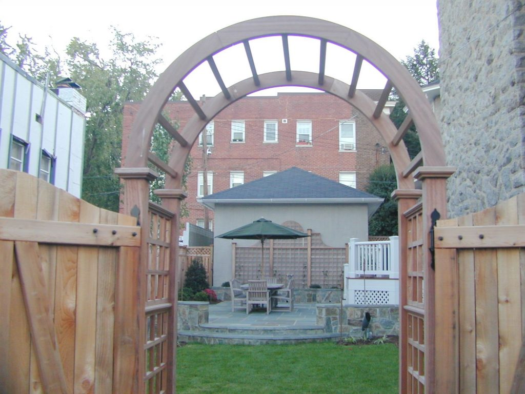 Wooden arbor leading into nice backyard with stone patio and seating area