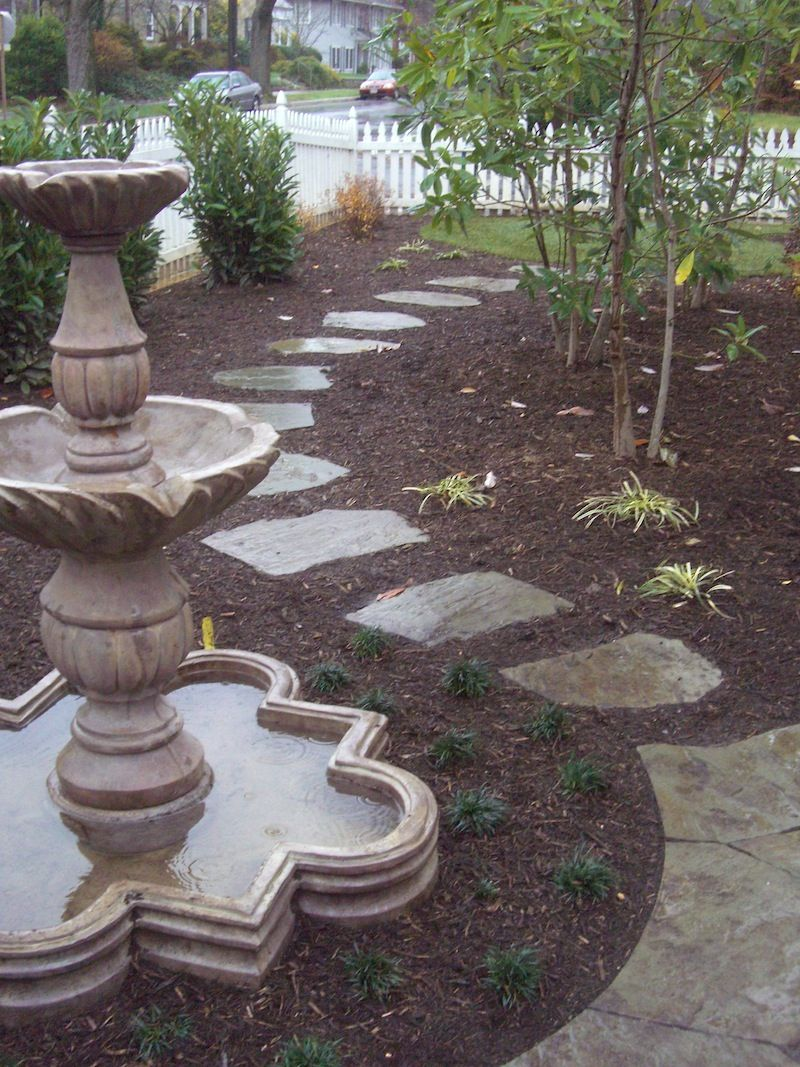 Stone paver walkway surrounded by brown mulch in front yard