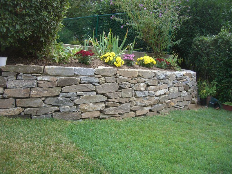 Stone wall surrounding mulch and flowers