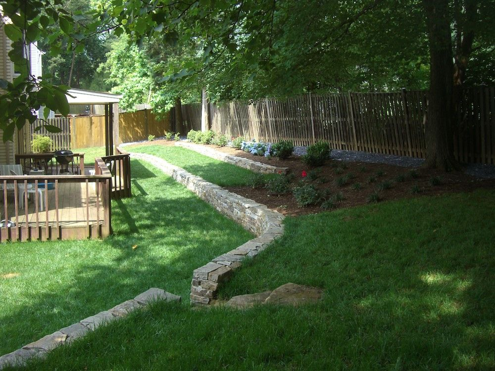 Backyard with stone walls and mulch