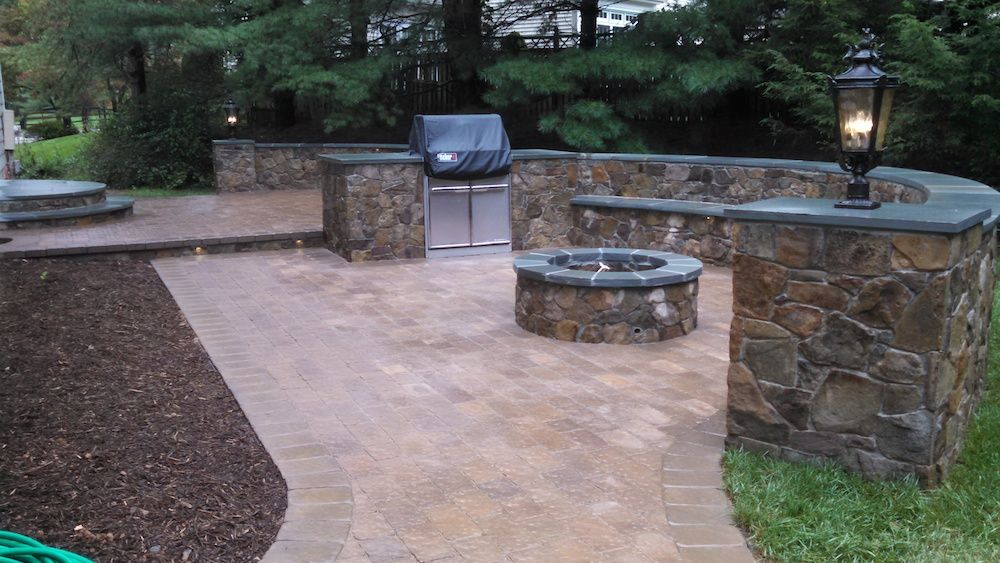 Patio with stone hedge, grill, and fireplace