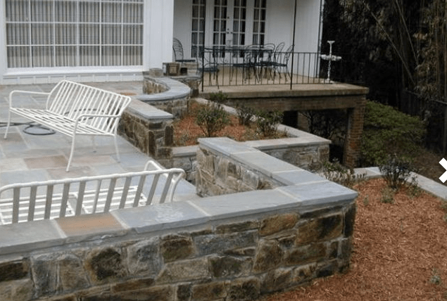 Patio surrounded by stone wall and mulch