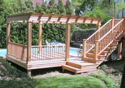 Large wooden pergola in front of large pool
