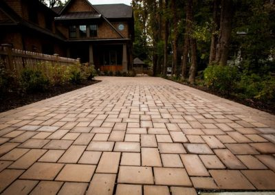 Stone paved driveway leading up to large house