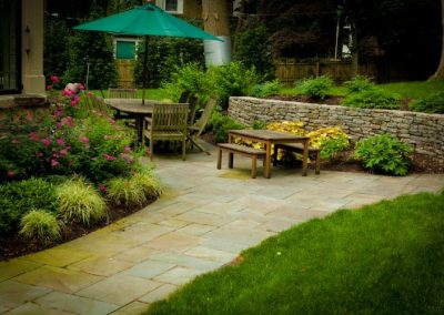 Stone patio with large outdoor dining table and picnic table next to stone wall
