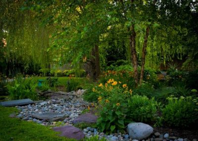 Backyard with stone path, flowers, greenery, and trees