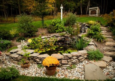 Large pond water feature in backyard surrounded by greenery and gravel