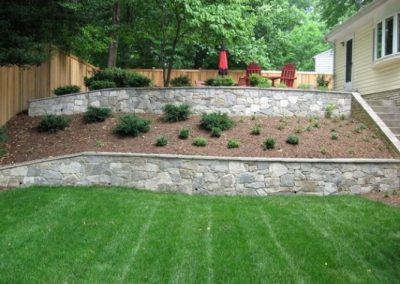 Stone retaining walls in backyard with multipel elevations