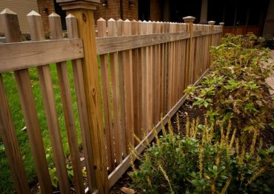 Wooden fence leading along driveway and landscaped area