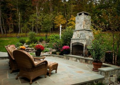 Stone patio with outdoor seating area and outdoor fireplace in backyard
