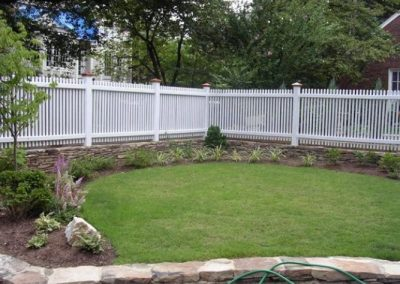 Backyard with white fence and several small plantings along edge of lawn