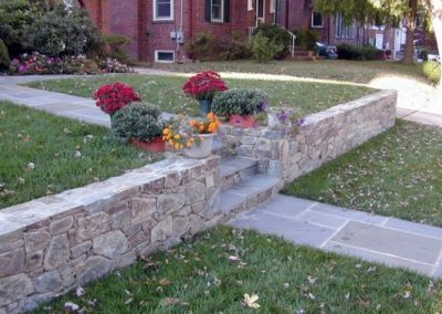 Stone retaining wall in front yard with flowers