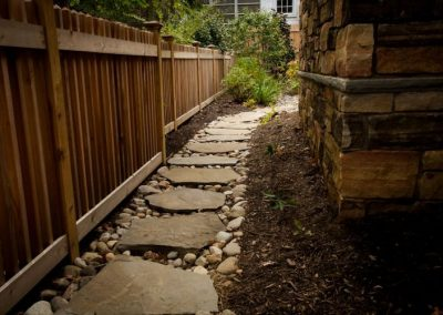 Stone pathway leading alongside house in gravel and mulch area