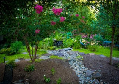 Backyard with stone gravel path, steps, plantings, and water features