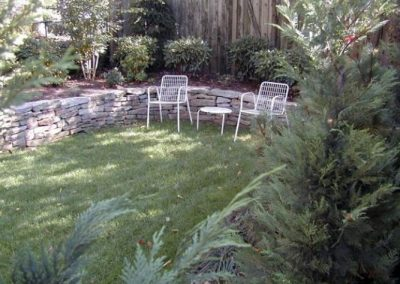 Low stone retaining wall in backyard seating area