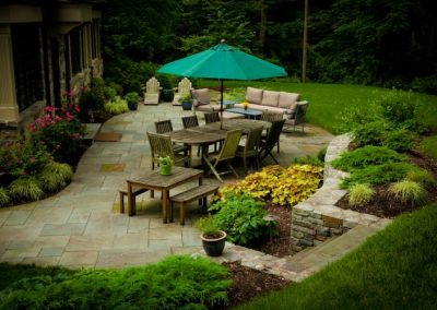 Stone patio with large outdoor dining table and picnic table next to stone house
