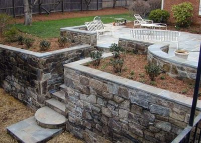 Large strone retaining wall in raised backyard patio area