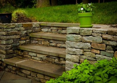 Stone decorative wall with steps in backyard