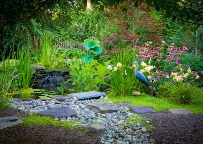 Backyard water feature with greenery and statues