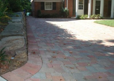 Stone paved driveway in front of red brick house