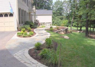 Stone pathway leading alongside a house in side yard with plantings