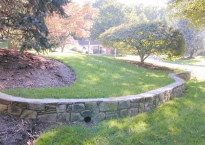 Small stone retaining wall in grass