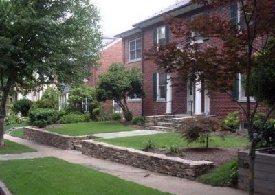 Low stone retaining walls in front yard of a large brick house