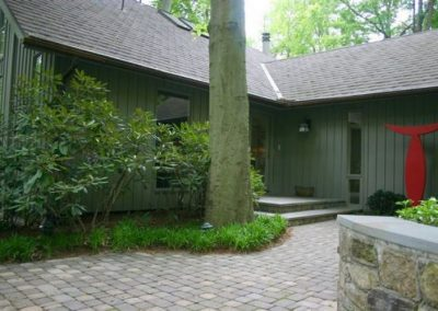 View of house with stone paved driveway