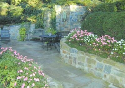 Beautiful backyard patio space with stone decorative walls, seating area, and greenery