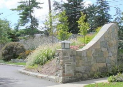 Outdoor stone retaining wall with landscaped plantings