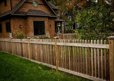 Wooden fence in front yard in front of brown house