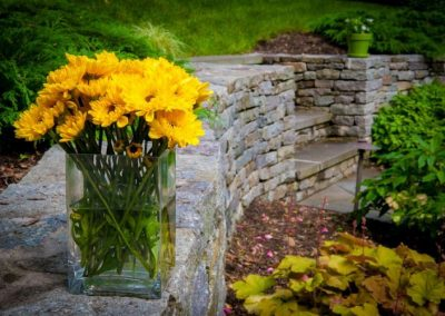 Yellow daises in vase on large stone decorative wall in backyard