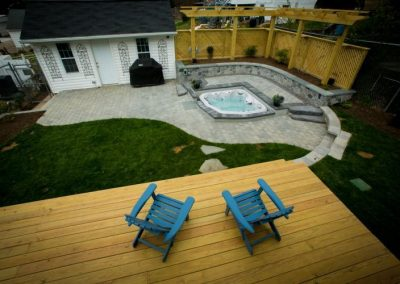 Aerial view of backyard with wooden patio, lawn, and stone patio with hot tub