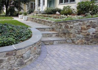 Stone driveway, decorative walls, and stone steps in front of house