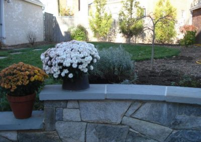 Backyard with flower plantings on stone wall