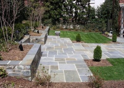 Large stone patio in landscaped backyard