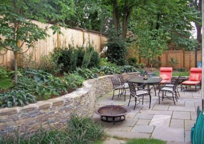 Backyard patio area with seating area, stone decorative wall, and shrubbery
