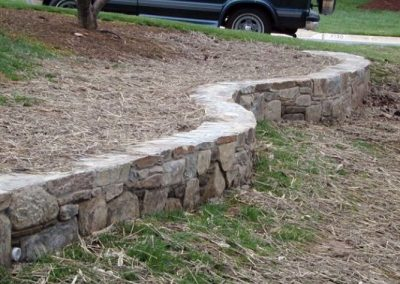 Low stone retaining wall in front lawn with grass and pine needles