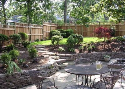 Beautifully landscaped backyard with seating area, low decorative stone walls, and greenery